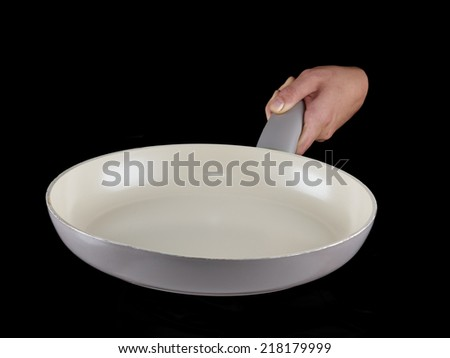 Woman's hand holding a frying pan isolated on black. - stock photo