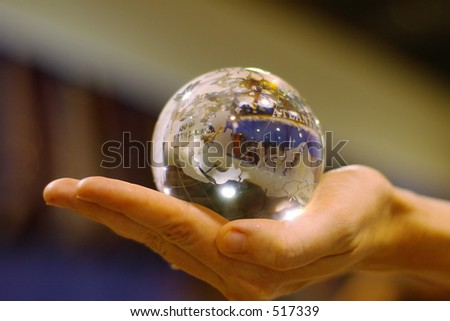 woman's hand holding a glass globe - stock photo