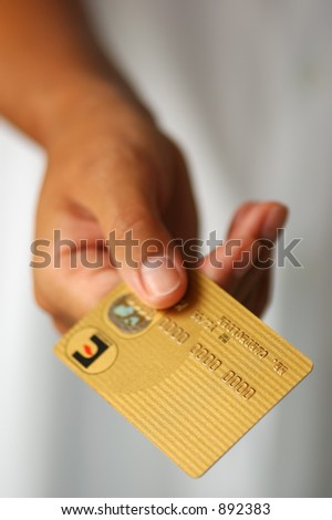 Woman's Hand Holding a Gold Credit Card - stock photo