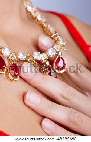 Woman's hand holding a necklace - stock photo