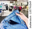woman's hand holding a new pair of jeans - stock photo