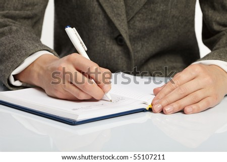 woman?s hand holding a pen