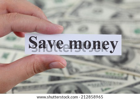 """Woman's hand holding a piece of paper with the words """"Save money"""" against dollar bill background. Close-up. - stock photo"""