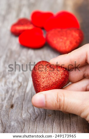 Woman's hand holding  a red heart shape. On wooden background.