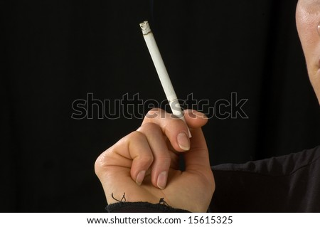 woman's hand holding a slim cigarette close up view