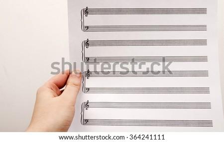 Woman's hand holding an empty music sheet. Start a musical education. - stock photo