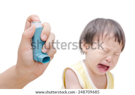 Woman's hand holding asthma inhaler foreground and crying baby sitting in background - stock photo