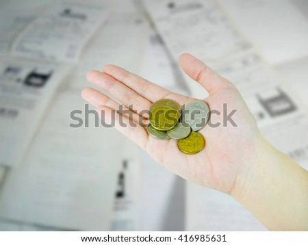 Woman's hand holding Australian coins on receipts background - stock photo