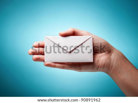 woman's hand holding closed envelope against blue background - stock photo