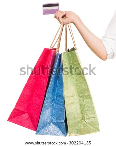 Woman's hand holding colored shopping bags and credit card on white background. Close-up. - stock photo
