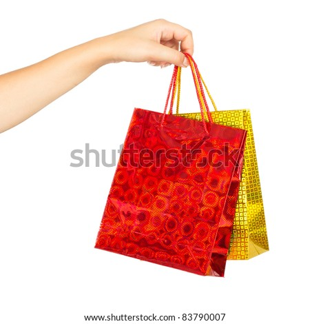 Woman's hand holding colorful shopping bags. Iisolated on white