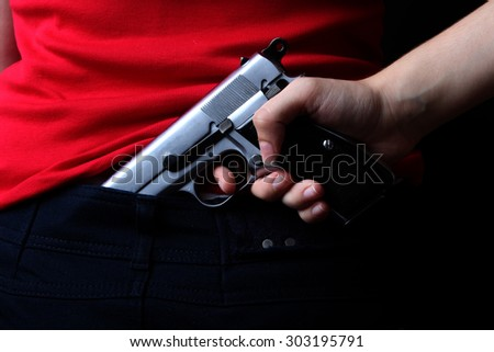 woman's hand holding handcuffs and a gun on a black background - stock photo
