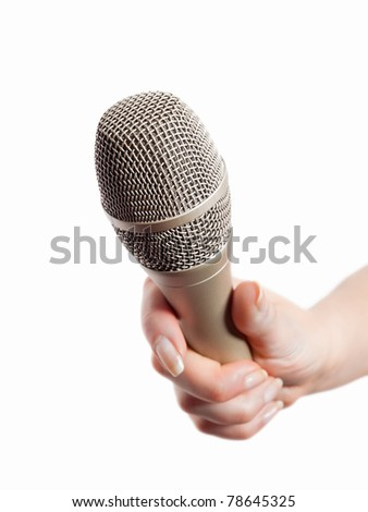 Woman's hand holding microphone isolated on white - stock photo
