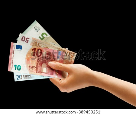 Woman's hand holding money isolated on black background