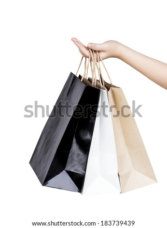 Woman's hand holding paper shopping bags isolated on white background