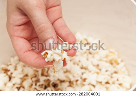 Woman's hand holding pop corns in a bowl. - stock photo