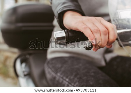 Woman's hand holding steering wheel