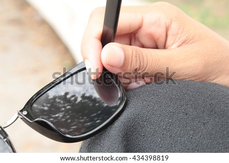 Woman's hand holding sun glasses in the park.