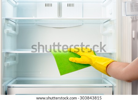 Woman's hand in yellow rubber protective glove cleaning white open empty refrigerator with green rag  - stock photo