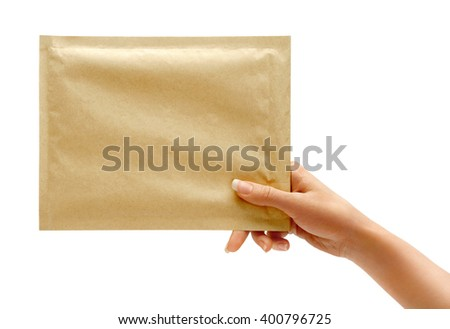 Woman's hand is giving envelope. Studio photography of woman's hand holding yellow envelope - stock photo