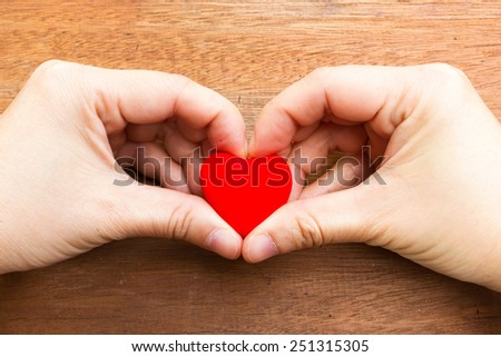 Woman's hand  make a heart shape and holding  a red heart shape. On wooden background.