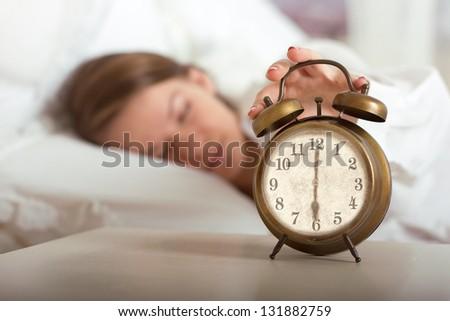 Woman's hand off the alarm clock, 6 am - stock photo