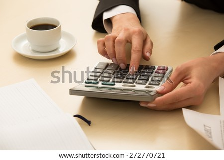 Woman's hand on calculator makes calculation. - stock photo