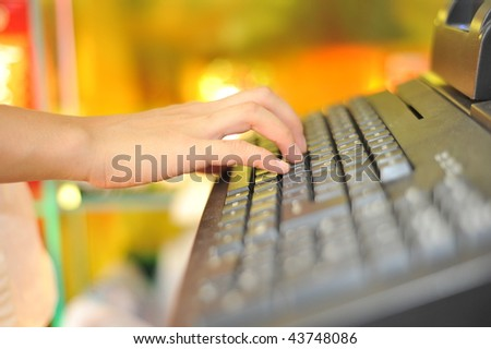 Woman's hand on cash register buttons - stock photo