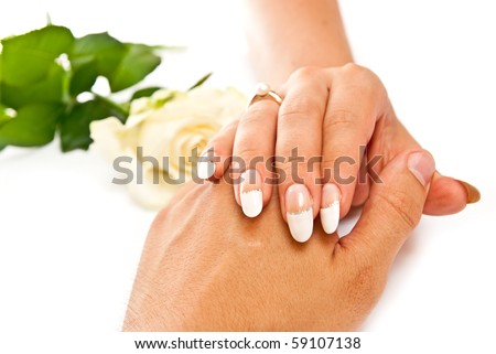 Woman's hand on man's with golden ring on white background - stock photo