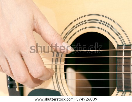 woman's hand on the guitar strings closeup - stock photo