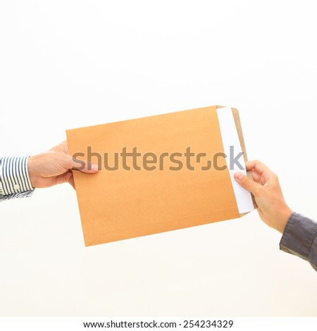 woman's hand passes a yellow envelope to male hand on white background view 3 - stock photo
