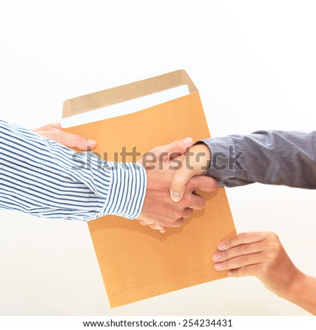 woman's hand passes a yellow envelope to male hand on white background view 2 - stock photo