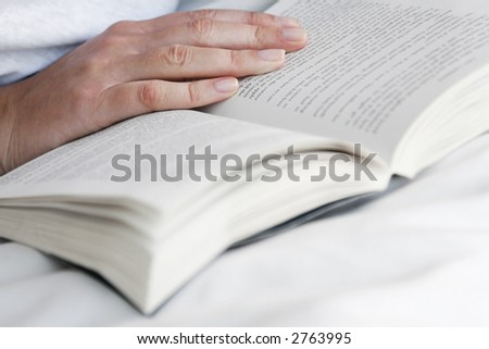 Woman's hand placed on open page of a book