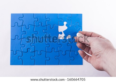 Woman's hand placing missing piece in Jigsaw puzzle  signifying problem solving and decision making - stock photo