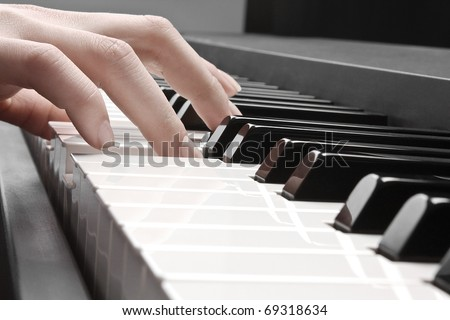woman's hand playing the piano - stock photo