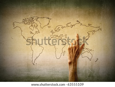 Woman's hand pointing at a country on a world map - stock photo