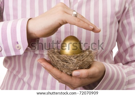 Woman?s hand protecting a nest with a golden egg inside - stock photo