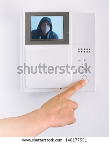 Woman's Hand Pushing a Button on a Security Pad with a pixelated image of a Suspicious Man on the Screen - stock photo