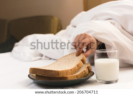 Woman's hand reaching from under duvet for breakfast in hotel.