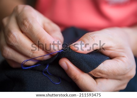 Woman's hand sewing fabric with sewing equipments - stock photo