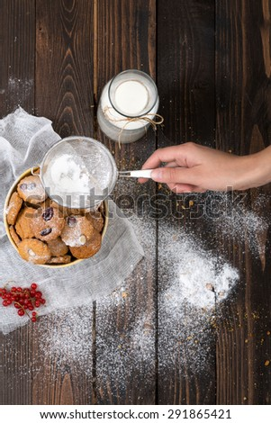 Woman's hand sprinkling icing sugar over cookies. Selective focus and small depth of field. - stock photo