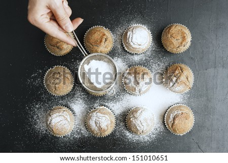 Woman's hand sprinkling icing sugar over fresh muffins. - stock photo