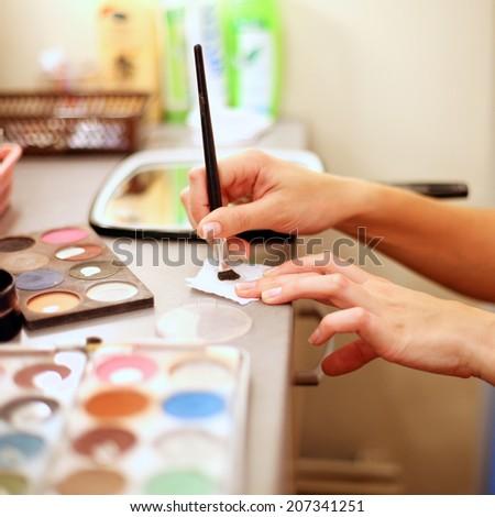 Woman's hand taking cosmetic paints with brush