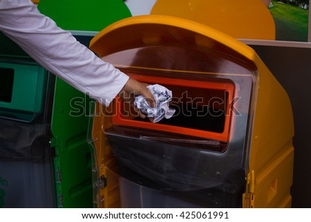 woman's Hand throwing bottle  into yellow  recycling bin, concept of environmental protection,  Littering of environmental. color coded trash bin for waste segregation - stock photo