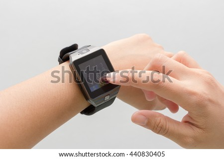 Woman's hand touching the screen of a smart watch  on white background.