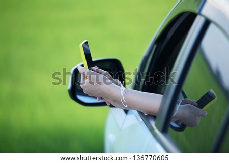 woman's hand using smart phone outside window car,conceptual for holiday,relax,navigator. - stock photo