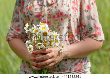 Woman's hand with a chamomile on sunny summer day