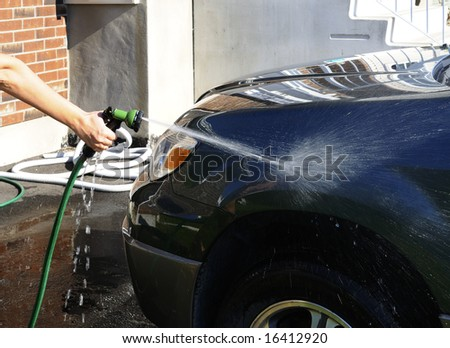 Woman's hand with a hose washing a car - stock photo