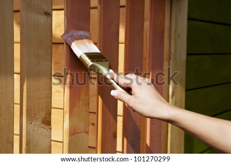 woman's hand with a paint brush painting wooden terrace in pink outdoor shot - stock photo