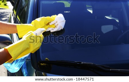 Woman's hand with a rag and glass cleaner washing windshield glass of an SUV car - stock photo